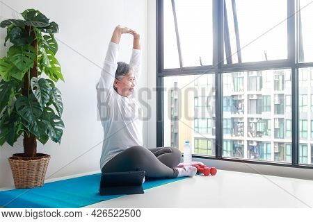 Asian Elderly Woman Sit Exercise At Home Do Yoga Poses According To An Online Fitness Teacher Via Vi