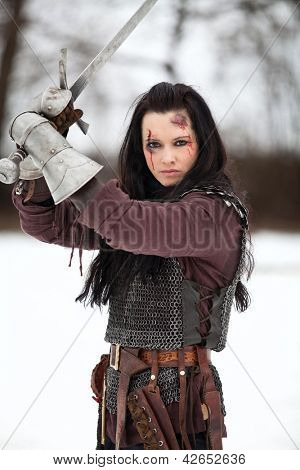 Woman in the medieval costume holding a sword poster