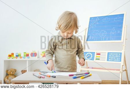 Cute Little Child Having Fun At Home Drawing With Colored Markers On Paper. Indoor Activity For Kids
