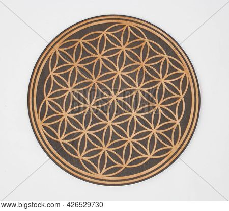 A Flower Of Life Wooden Board Photographed Against A White Background