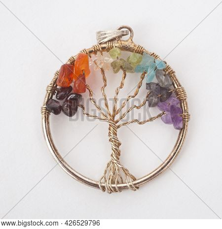 A Tree Of Life Pendant With Chakra Crystals Photographed Against A White Background