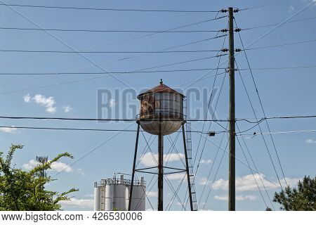 Vintage Water Tower And Power Poles And Lines Blue Sky Background