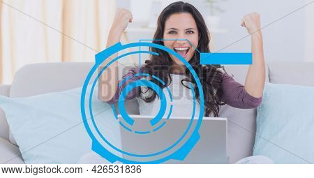 Composition of scope and digital screen over woman celebrating using laptop. global business, digital interface, technology and networking concept digitally generated image.