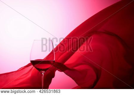 Glass Of Red Wine On A Background Of Waving Red Satin Curtain.
