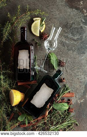 Vintage Bottles Of Gin And Various Ingredients On An Old Stone Table. There's A Blank Label On The B