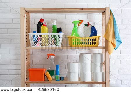 Shelving Unit With Detergents And Toilet Paper Near White Brick Wall