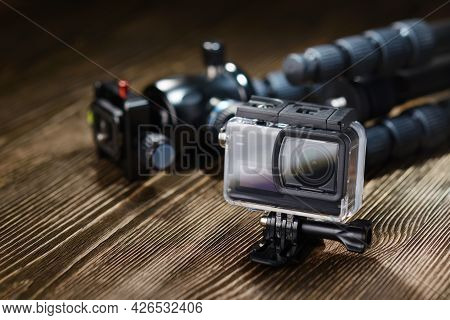 Black Small Action Camera In Waterproof Housing And Tripod On Brown Wooden Tabletop.