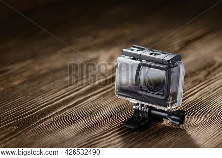 Black Small Action Camera In Waterproof Housing On Brown Wooden Tabletop.
