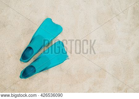 Pair Of Blue Flippers On Sand Background, Top View. Swimming Equipment - Fins On Shore. Summer Vacat