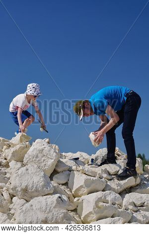 Russia, Moscow Region, 10.07.2021 - Dad And Son Are Looking For Fossils. Family Hobby Is Paleontolog