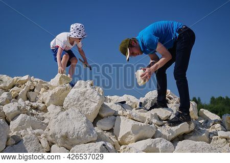 Russia, Moscow Region, 10.07.2021 - Dad And Son Are Looking For Fossils. My Family Hobby Is Paleonto