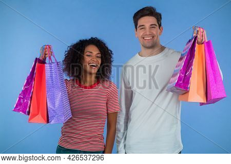 Interracial Shopaholic Couple Holds Shopping Paper Bags On Blue Studio Background. White Man And Afr