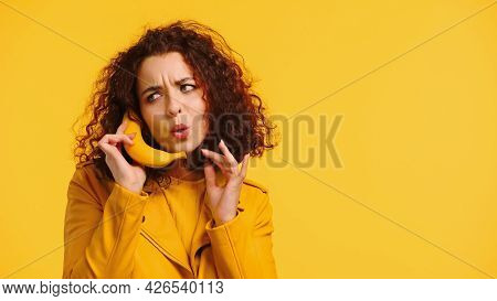 Young Woman Imitating Phone Conversation With Banana Isolated On Yellow