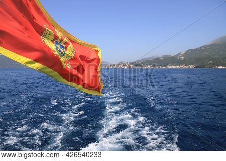 Flag With Coat Of Arms Of Montenegro Flies Over Kotor Bay, Beautiful Landscape. Summer Vacation And