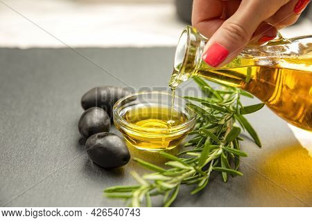 Olive Oil. A Woman Pours Olive Oil Into A Saucer.