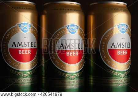 Beer Cans. Amstel Beer In Cans Close-up. A Number Of Cans On A Brown Background. The World-famous Br
