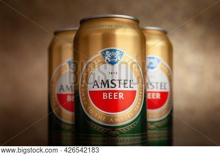 Beer Cans. Amstel Beer In Cans Close-up. A Row Of Cans On A Brown Background. The World-famous Brand