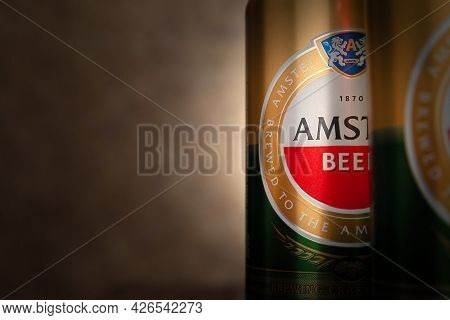Beer Cans. Amstel Beer In Cans Close-up On Brown Background With Copy Space. An Internationally Reno