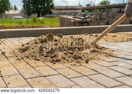 Close-up Of A Shovel In The Hands Of A Man Picking Up Sand From A Large Pile To Scatter It Through T