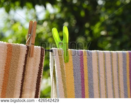 Close-up Of Towels With Clothespins Hanging On A Clothesline Outdoors. Summer Time.