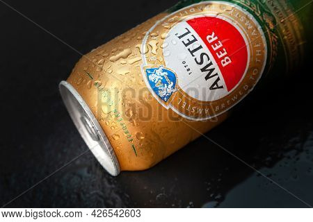 Beer Can With Water Drops. Amstel Beer In A Wet Can On A Wet Black Surface. An Internationally Renow