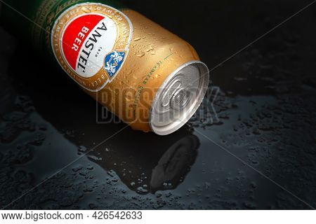 Beer Can With Water Drops. Amstel Beer Close-up In A Wet Can. World Famous Dutch Brand. Black Wet Ba