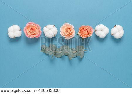 Flower Composition. A Border Of Cotton Flowers, Rose Heads And A Branch Eucalyptus On A Blue Paper B