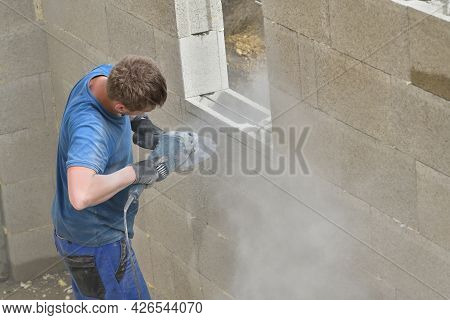 Brick Wall Made Of Blocks And Sawing A Hole In A Window Made Of Blocks Using A Grinder