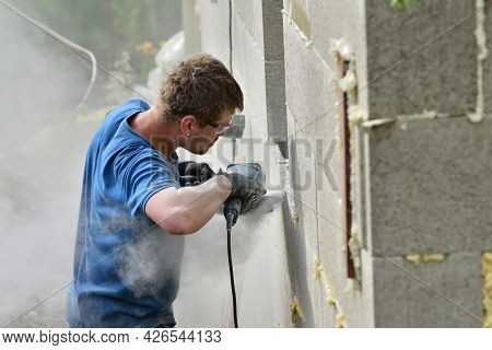 A Grinder On A Construction Site Saws Bricks Using An Electric Grinder In Dust
