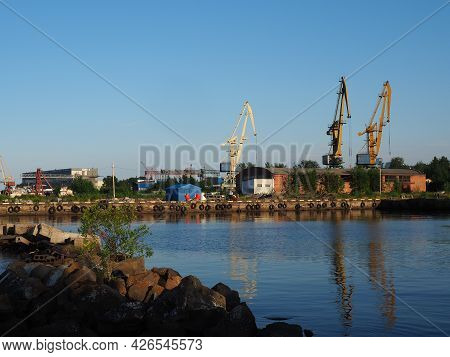 Petrozavodsk, Russia, July 10, 2021. Port with cargo cranes and ships. Pleasure wooden yachts and bo