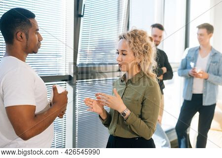 Portrait Of African American Male Having Conversation With Young Woman Colleague, Selective Focus. G