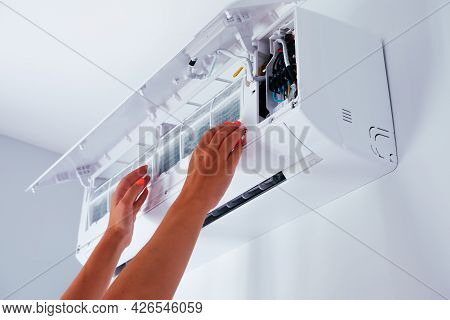 Repair Service Of The Air Conditioner. The Woman Removes The Air Conditioner Filter. View Of The Han