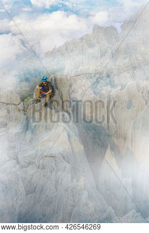 Hiker With Backpacks Reaches The Summit Of Mountain Peak. Male Traveler On High Top Of Rock Enjoying