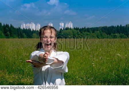 Teenage Girl Practicing Karate Kata Outdoors, Performs Nukite Tsuki Strike With Kiai Scream