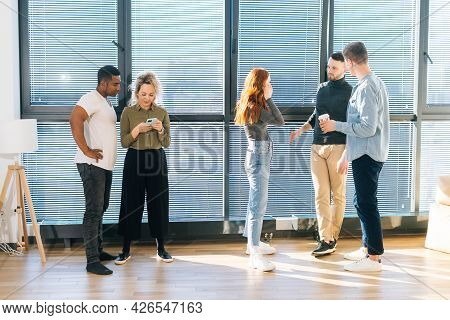Front View Of Young Multiethnic Coworkers Having Fun Conversation During Coffee Break In Modern Offi