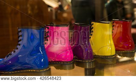 Five Shining Boots In A Row In A Storefront. Same Model, Five Different Colours: Blue, Pink, Lila, Y