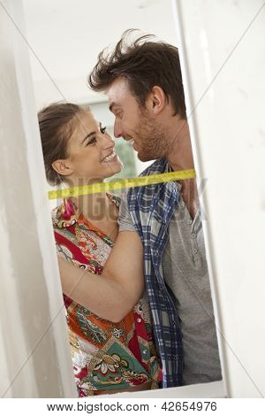 Loving couple renovating home, measuring by ruler, smiling happy.