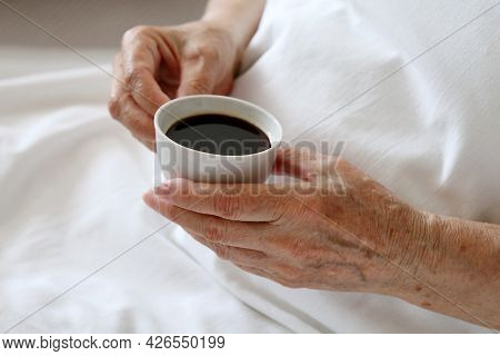 Elderly Woman With White Cup Of Black Coffee In Wrinkled Hands In A Bed. Concept Of Fresh Morning, E