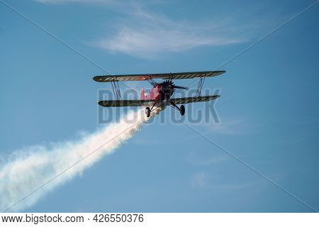Biplane Airplane Flies In A Picturesque Cloudy Sky. Old School Aircraft Aviation