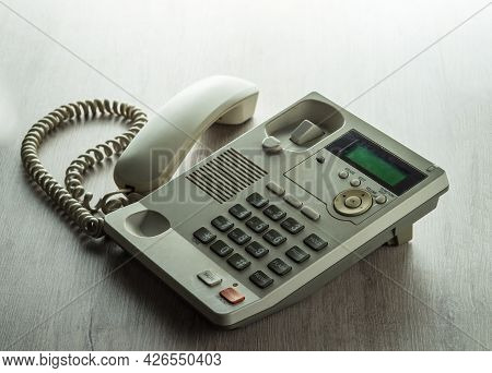 Black Landline Phone With Buttons On The Table. On A White Background.