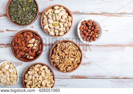 Different Kind Of Nuts In Wooden Bowls Such As Cashew Nuts, Hazelnuts, Walnuts, Blanched Almonds, Br