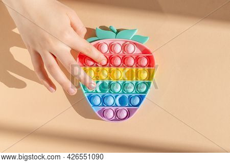 Had Is Using Rainbow Push Pop It Bubble Sensory Fidget Toy In Form Of Strawberry, Sensory Silicone T