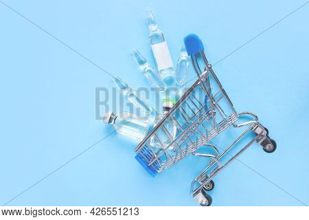Medicine Concept. Various Glass Ampoules, Packaging Of Medicines In A Shopping Cart With Bottles Wit