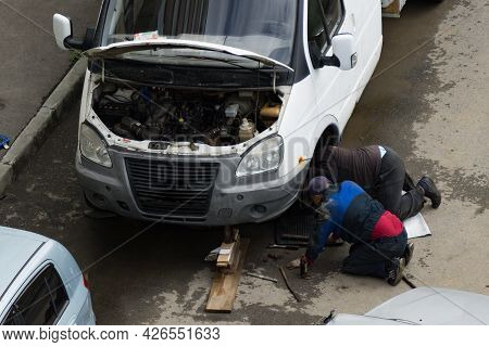 Two Men On The Street Repair A Truck. Jack And Tools Next To The Machine. Men Change The Wheel Of A