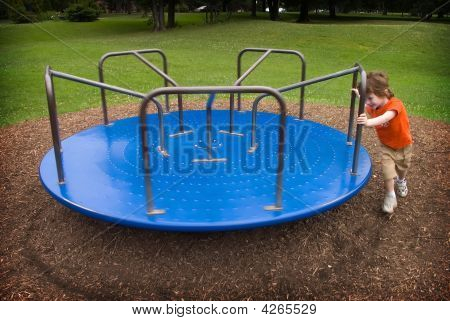 Boy Pushes A Merry-go-round