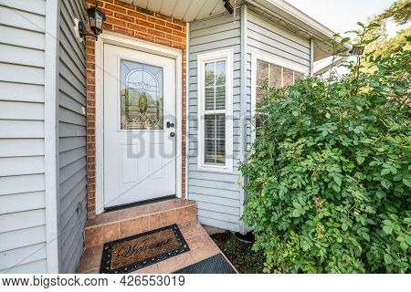 Front Door Exterior With Bricks And Vinyl Siding Wall