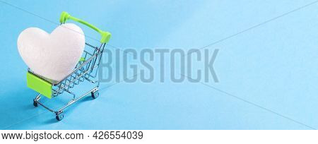 White Heart In Shopping Baskets On A Blue Background. Buy Love, Buy A Heart