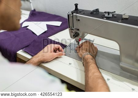 Cropped View Of Blurred Tailor Using Sewing Machine While Working In Atelier