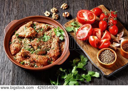 Chakhokhbili, Stewed Chicken, Tomato With Fresh Herbs, Walnuts And Spices In A Clay Pot On A Wooden