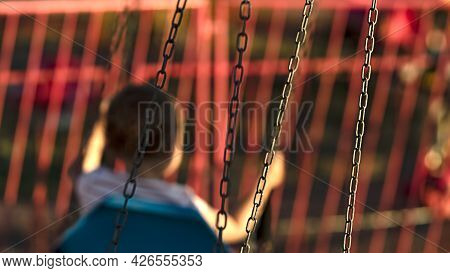 Blurred Silhouette Of A Little Child Riding A Carousel On Chains In Focus